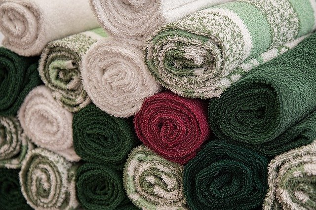 Soft-looking towels neatly rolled and arranged. | Source: Pixabay