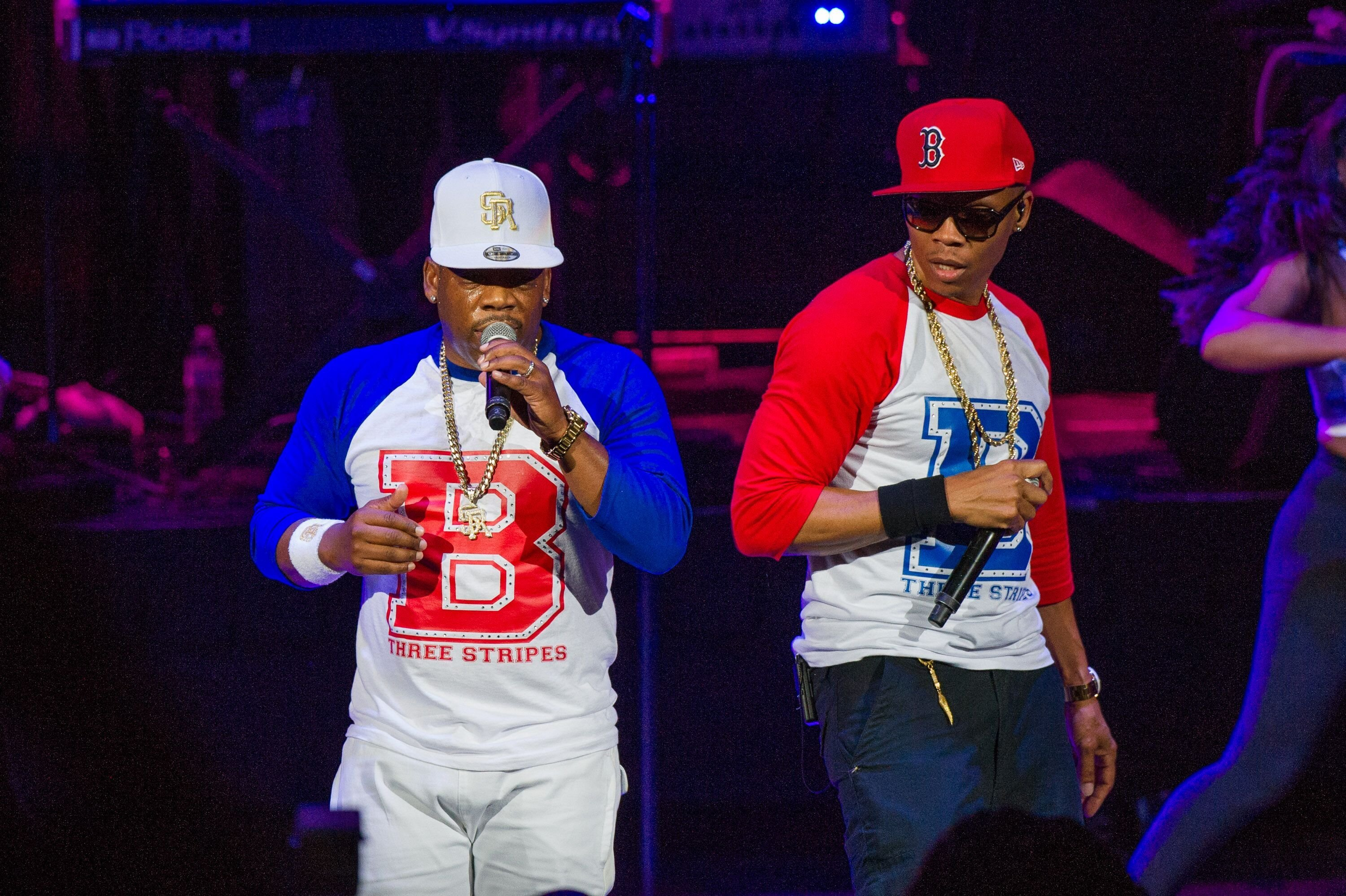 """New Edition"" members performing onstage at a concert 
