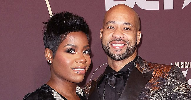 Fantasia Displays Legs Rocking Short Jumpsuit, Boots & Jacket in Black & White Pic with Husband