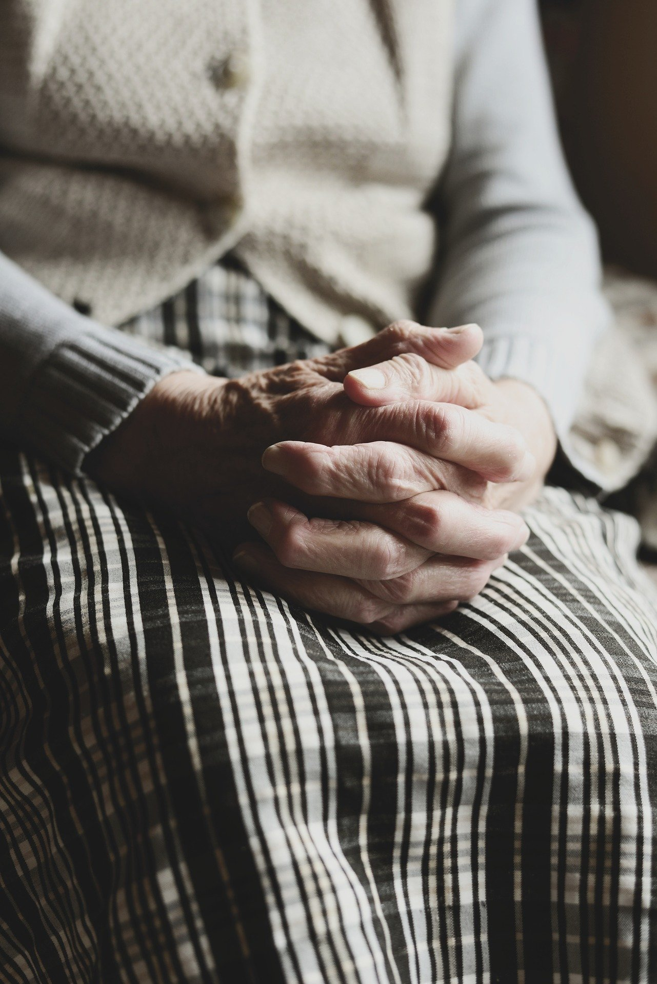An old woman sitting with her hands clasped together   Photo: Pixabay/congerdesign
