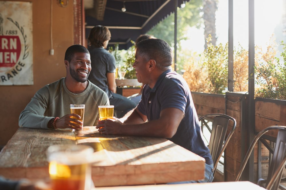 Two men drinking beer at a bar. | Photo: Shutterstock