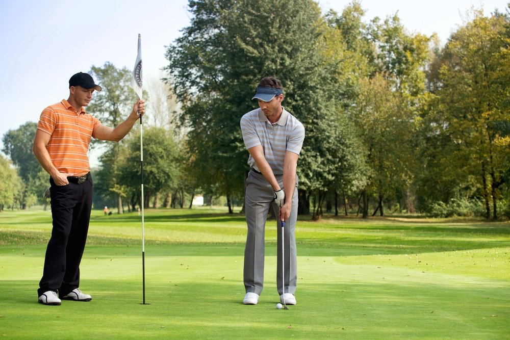 Two young men playing golf in golf course. | Photo: Shutterstock