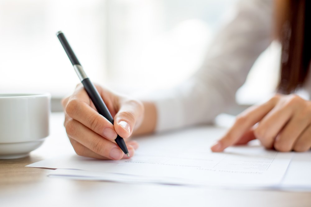 Hand of businesswoman writing on paper in office. | Photo: Shutterstock