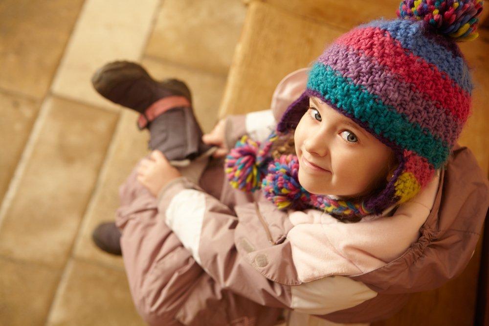 Une fillette souriante enfile ses bottes | Photo: Shutterstock