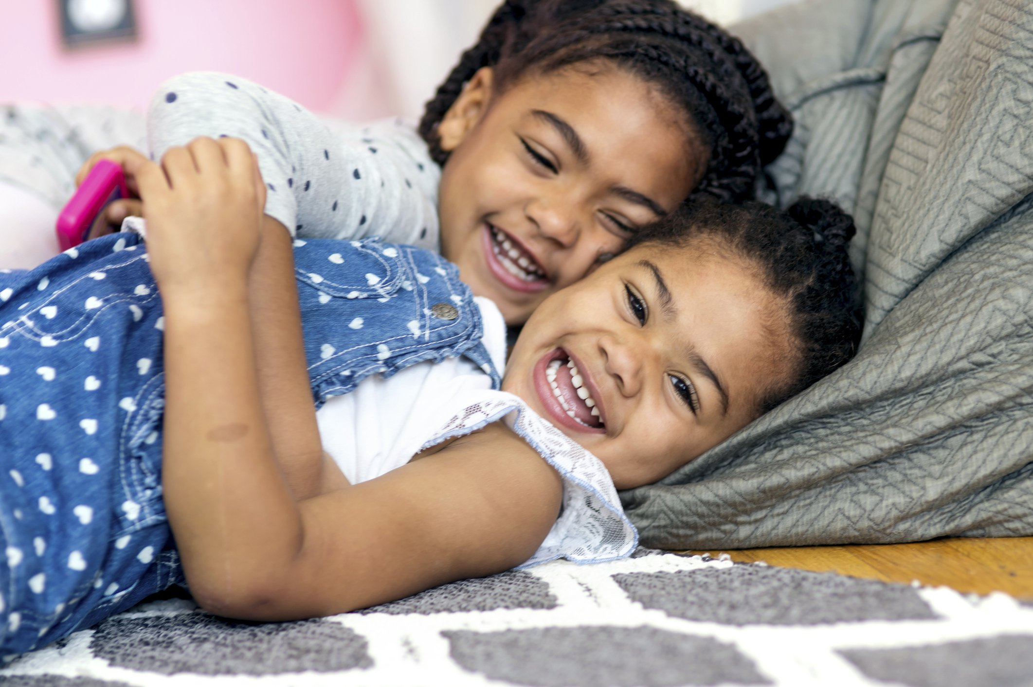 Cute African American girl tickling younger sister on the floor | Photo: Getty Images