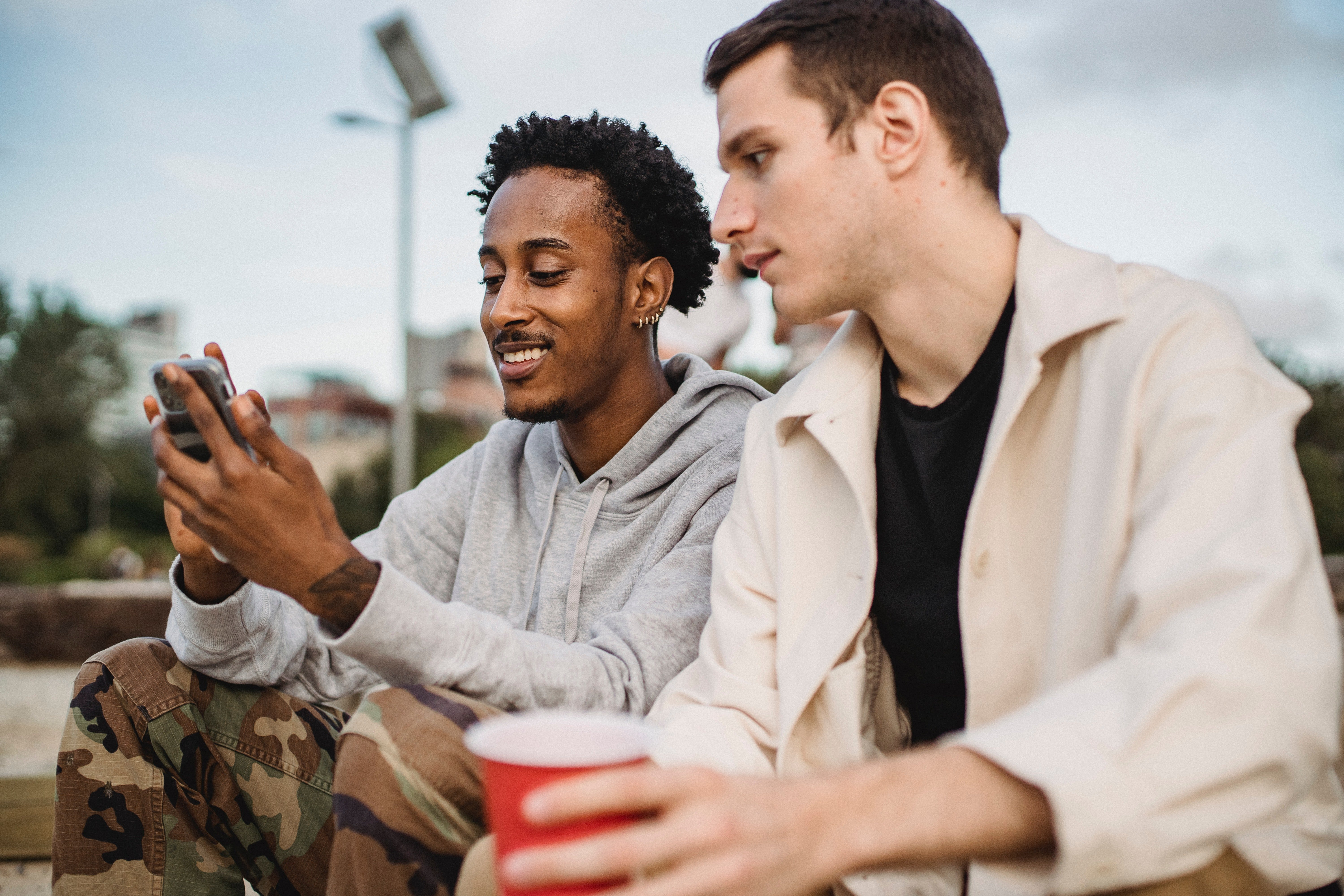 Cheerful man showing his phone to a friend  | Photo: Pexels
