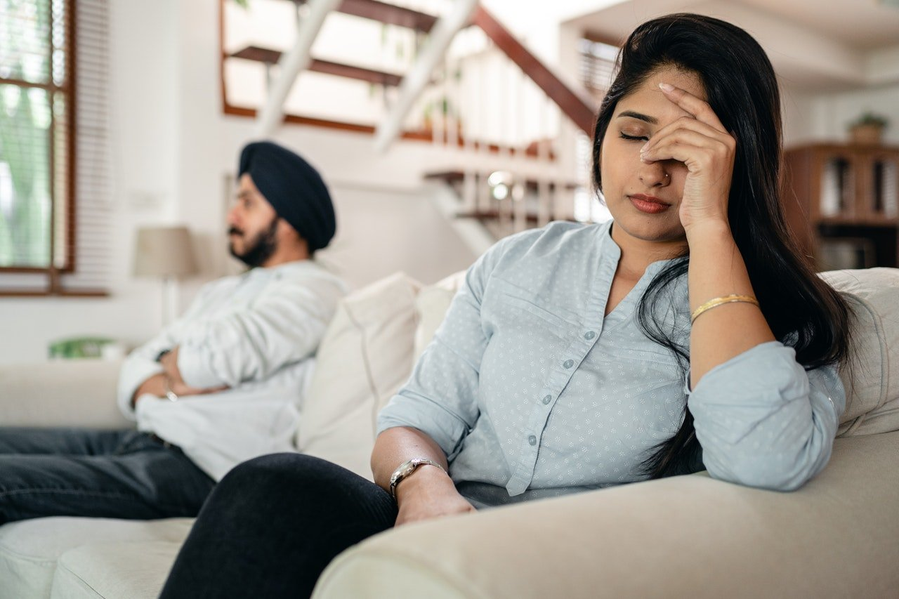 Man and woman sits on couch with woman holding her head in exasperation | Photo: Pexels