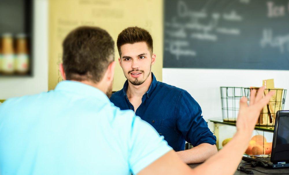 Hombre molesto habla con otro en restaurante.    Fuente. Shutterstock