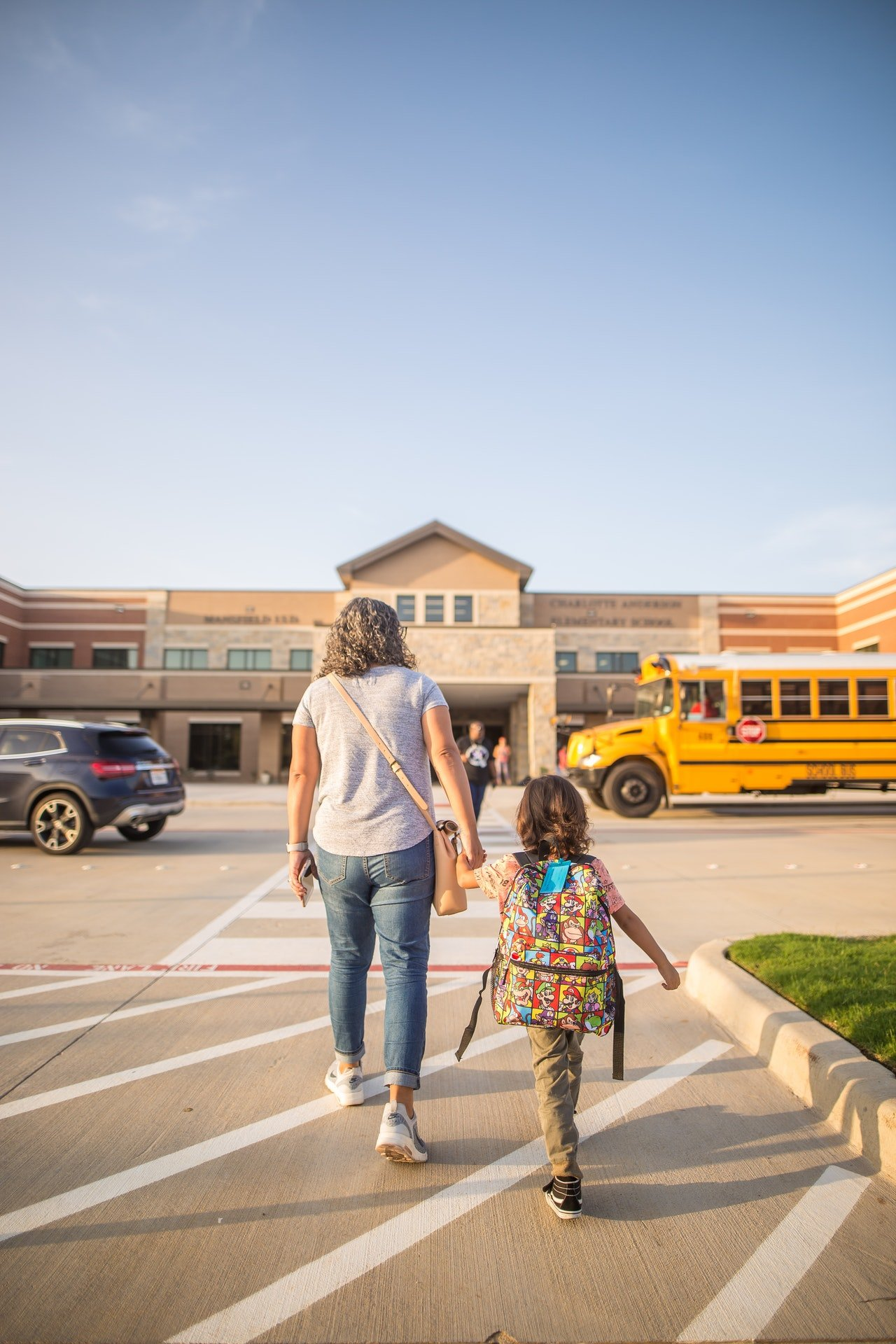 A woman and her daughter crossing the road to school | Source: Pexels