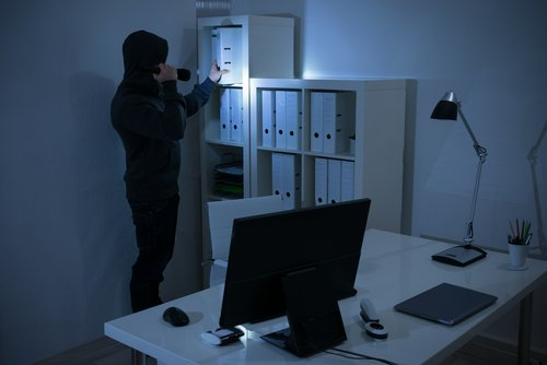 A robber seaching for valuables by flashlight. | Source: Shutterstock.