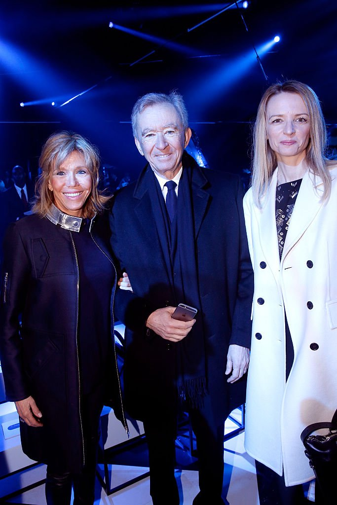 Brigitte Macron, Bernard Arnault et Delphine Arnault lors du défilé Louis Vuitton de la Fashion Week de Paris le 9 mars 2016. l Source : Getty Images