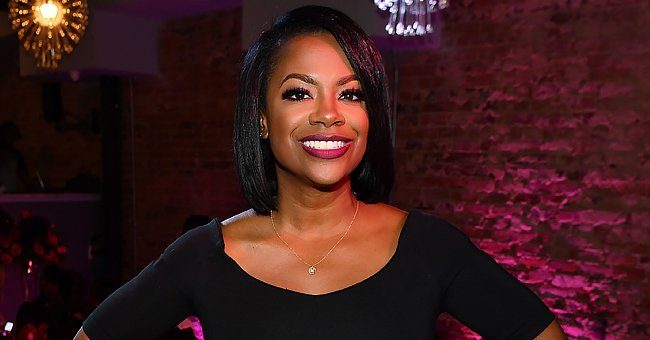 RHOA's Kandi Burruss Shows Cleavage & Long Leg in a Plunging Pink Dress with a Thing-High Slit