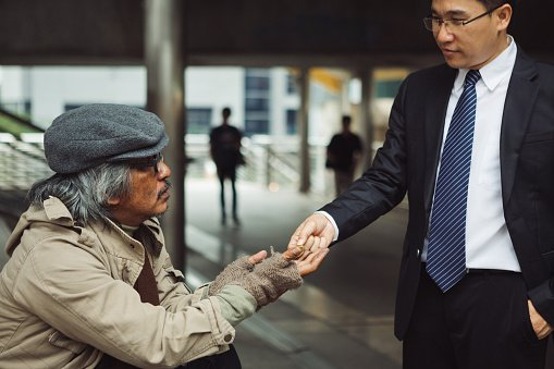 Photo of a business man giving money to a homeless man   Photo: Getty Images