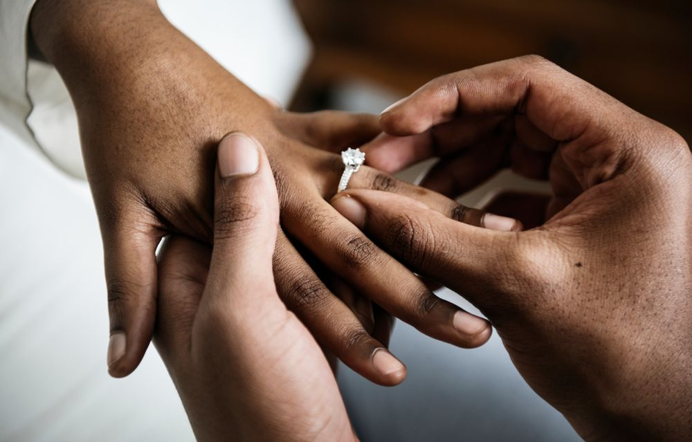 A newly engaged man putting the ring on his fiancee's finger. | Source: Shutterstock