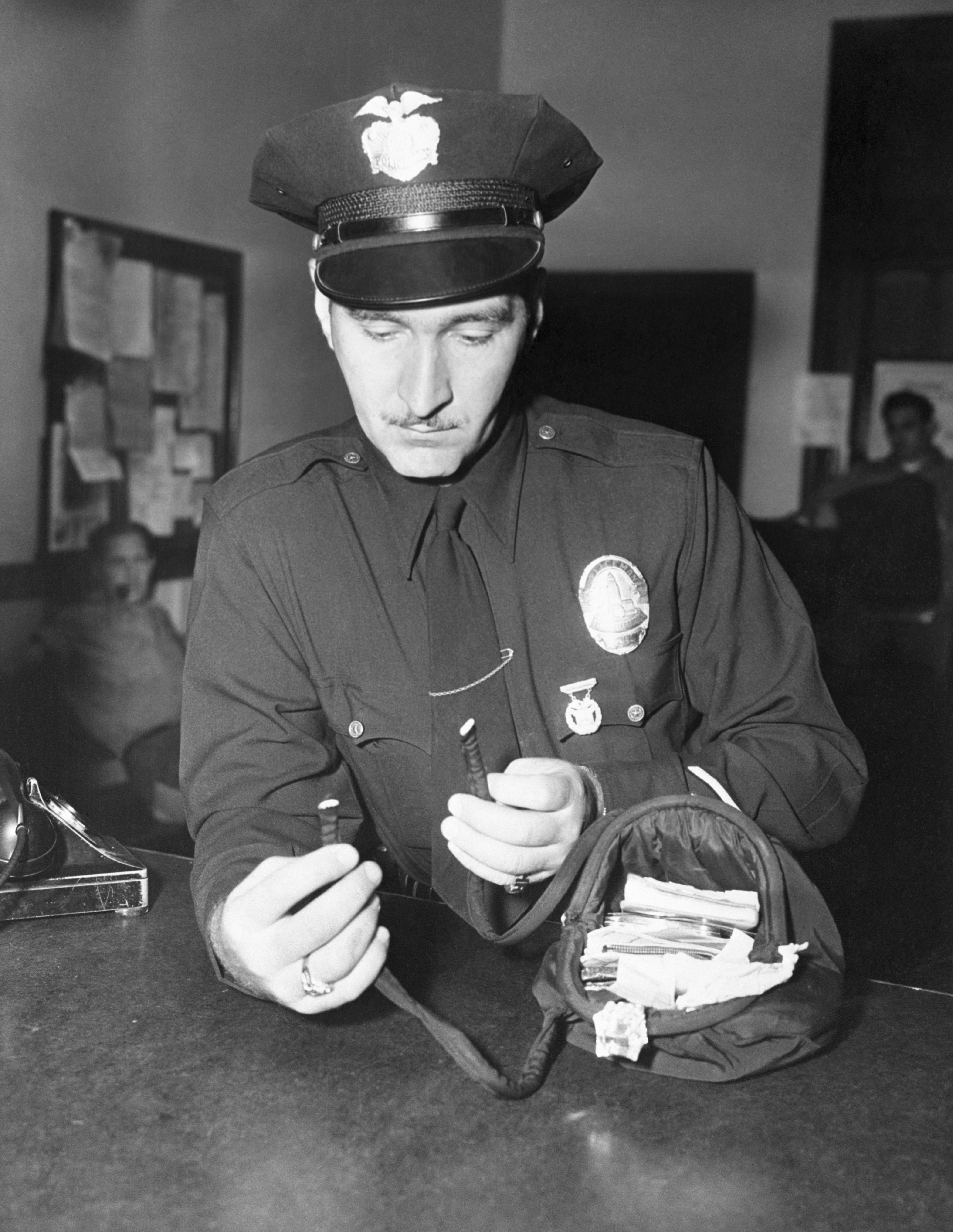 Officer Howard Rose holding Jean Spangler's damaged purse, which was taken in as evidence, 1949 | Photo: Getty Images