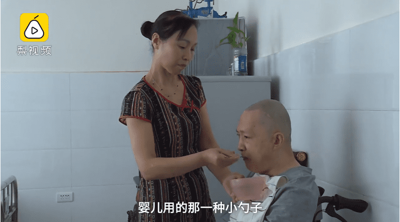 Zhang Guihuan en train d'aider son  à se nourrir. | Photo : capture/Vidéo