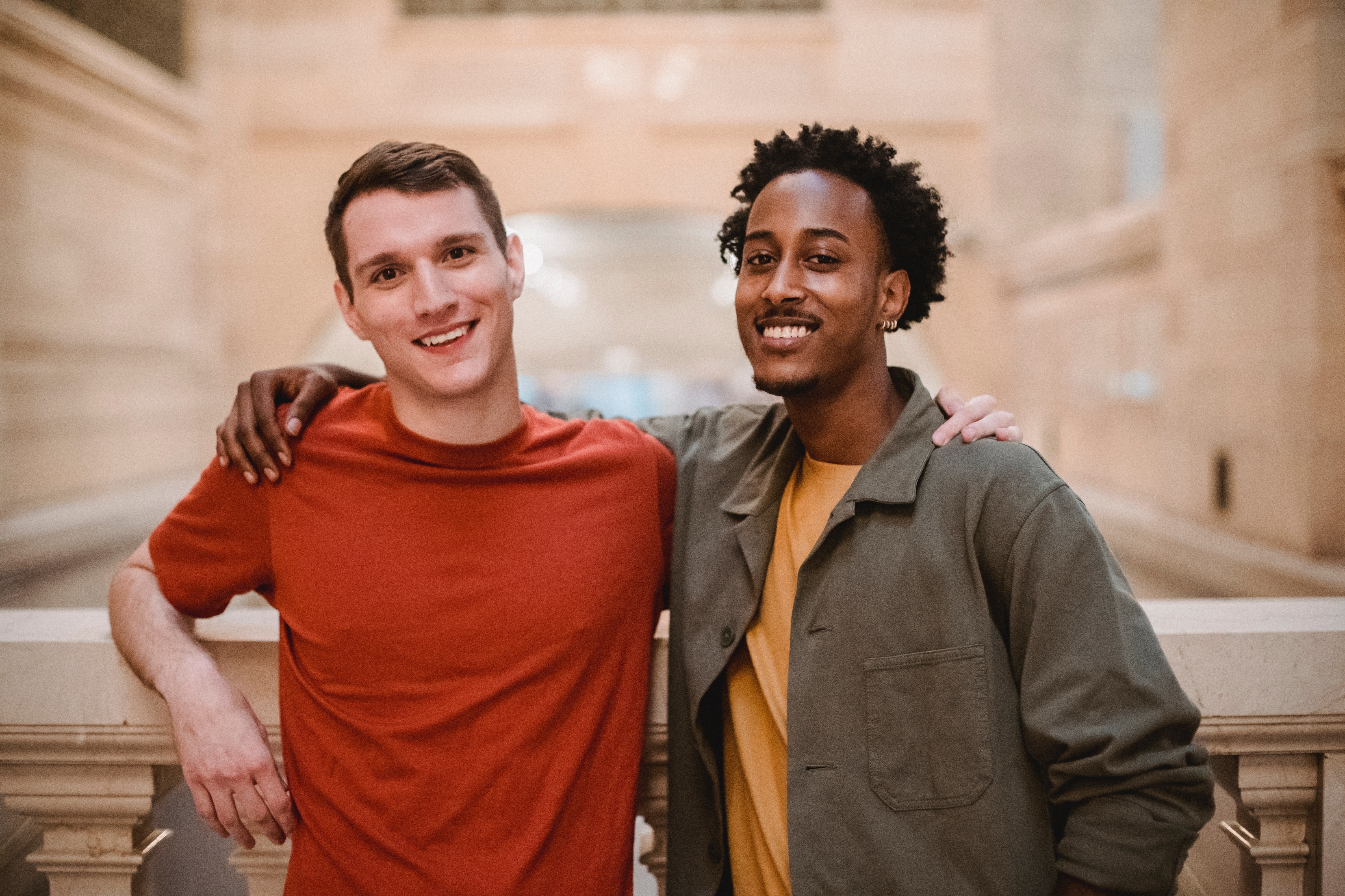 Two smiling male friends with their arms around each other | Photo: Pexels