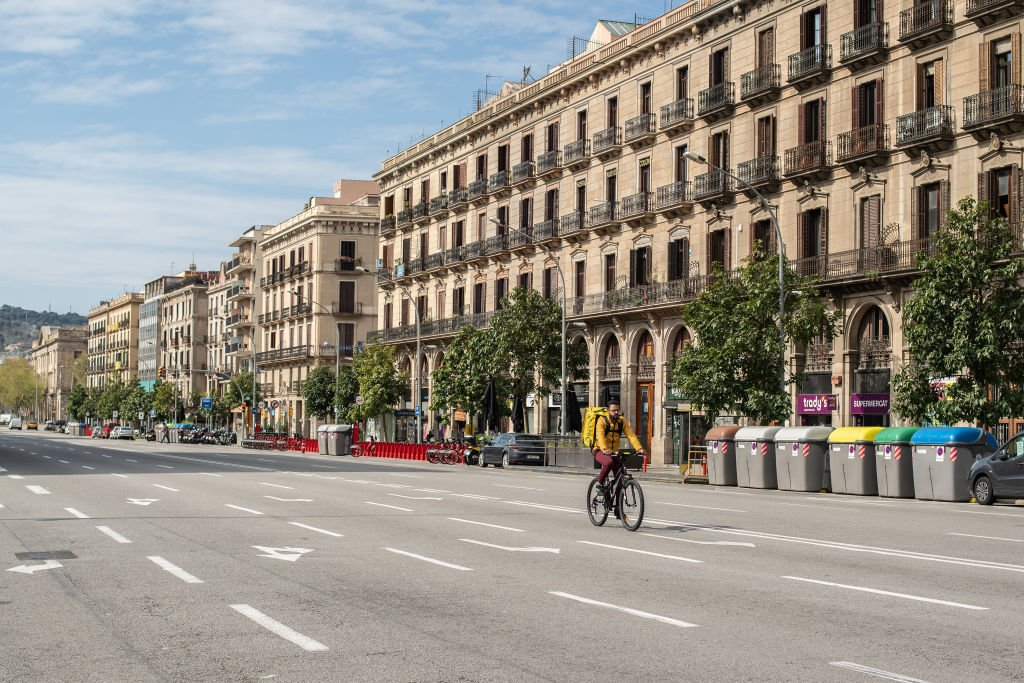 A glove delivery worker rides his bike on an empty street on March 27, 2020 in Barcelona, Spain. | Photo: GettyImages