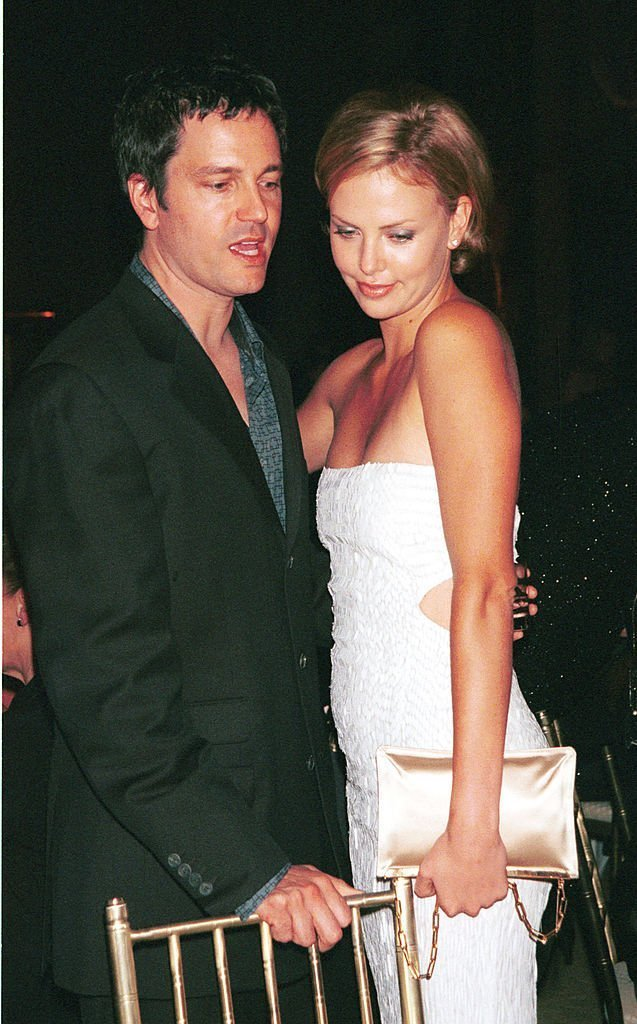 """Charlize Theron cuddles up with her boyfriend Stephan Jenkins October 24, 2000 during The Fashion Group International's presentation of """"Night of Stars 2000""""
