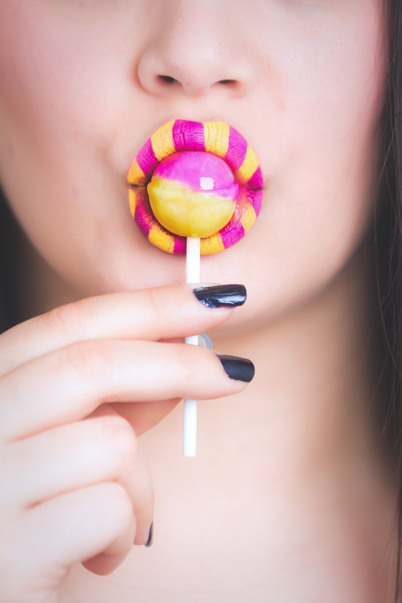 Photo of a woman licking lollipop | Photo: Pexels