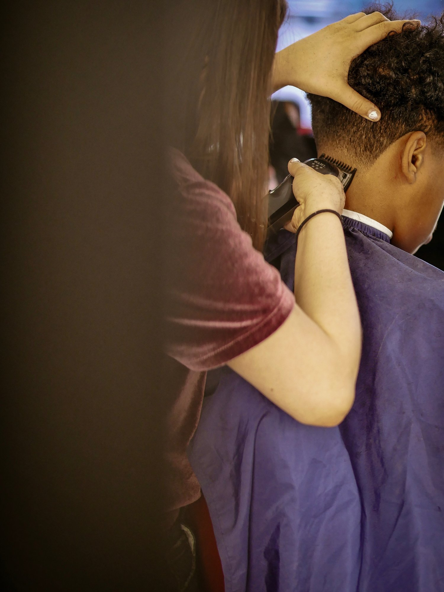 Woman shaving head of a boy at the  barber shop | Photo: Getty Images