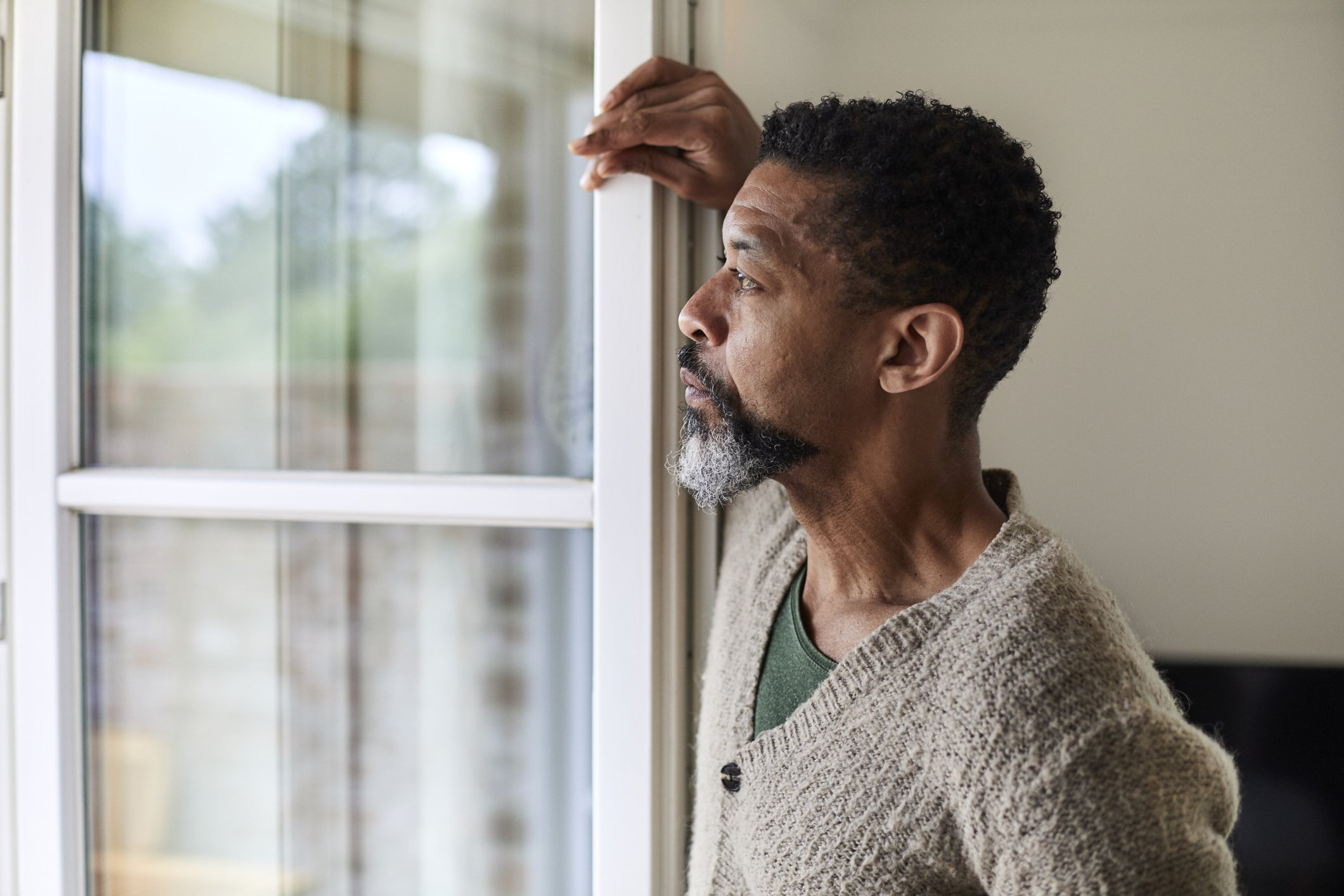 A worried man looks out the window in deep thought. | Photo: Getty Images