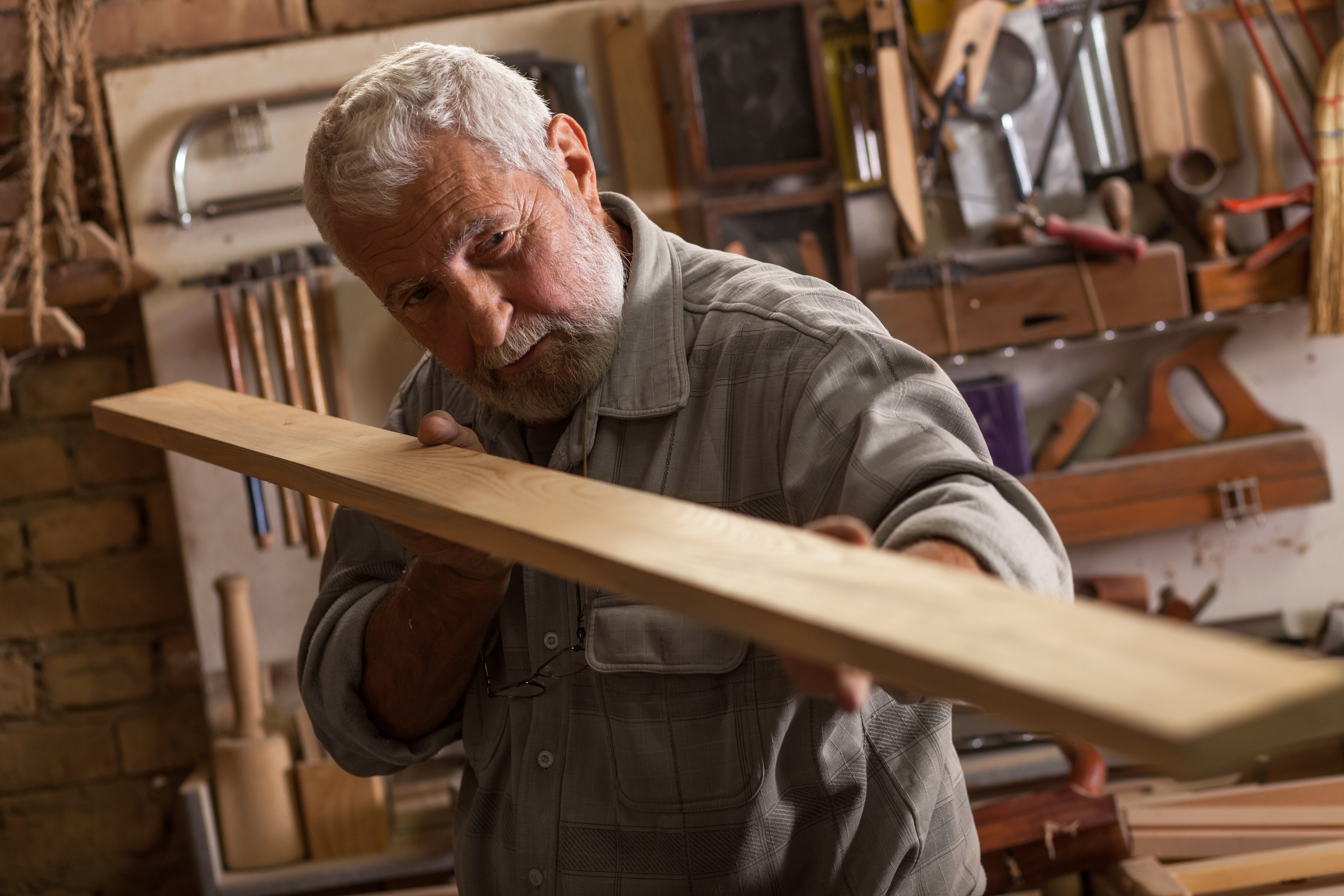 An old carpenter working on his craft | Photo: Shutterstock