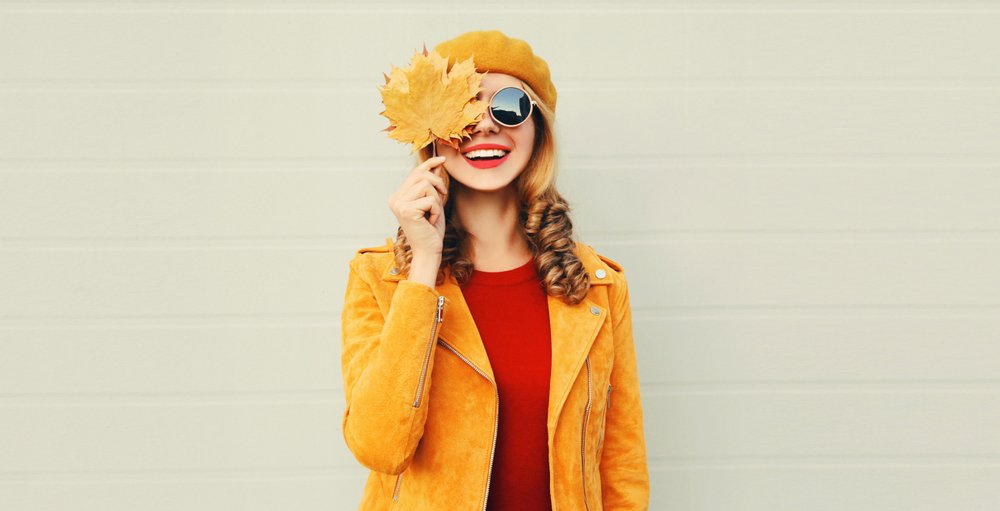 A happy smiling woman holding in her hands yellow maple leaves. | Photo: Shutterstock