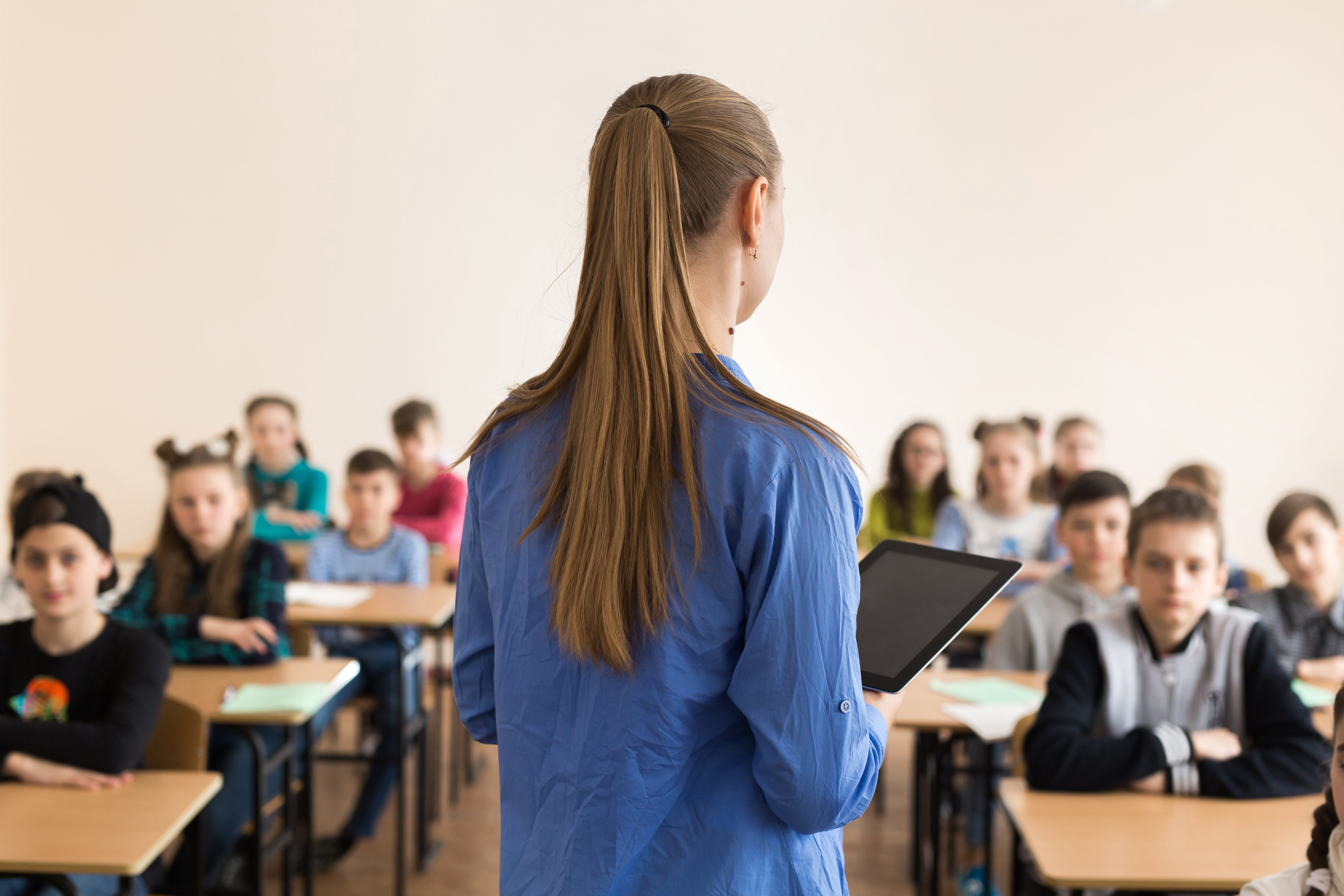 Teacher at the front of her class. | Photo: Shutterstock