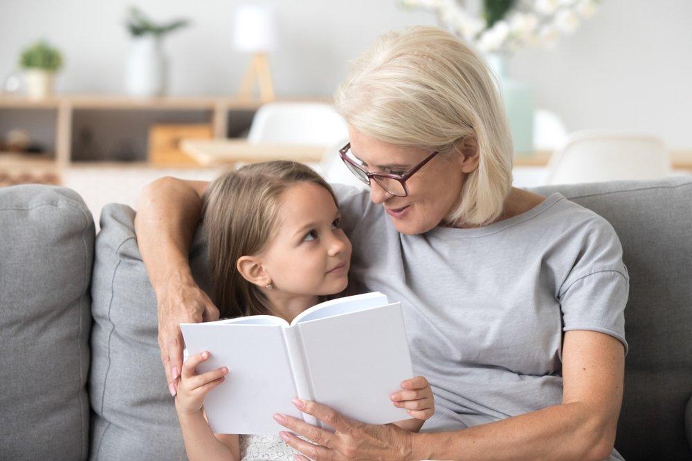 Abuela amorosa leyendo un cuento de hadas a su nieta. | Fuente: Shutterstock