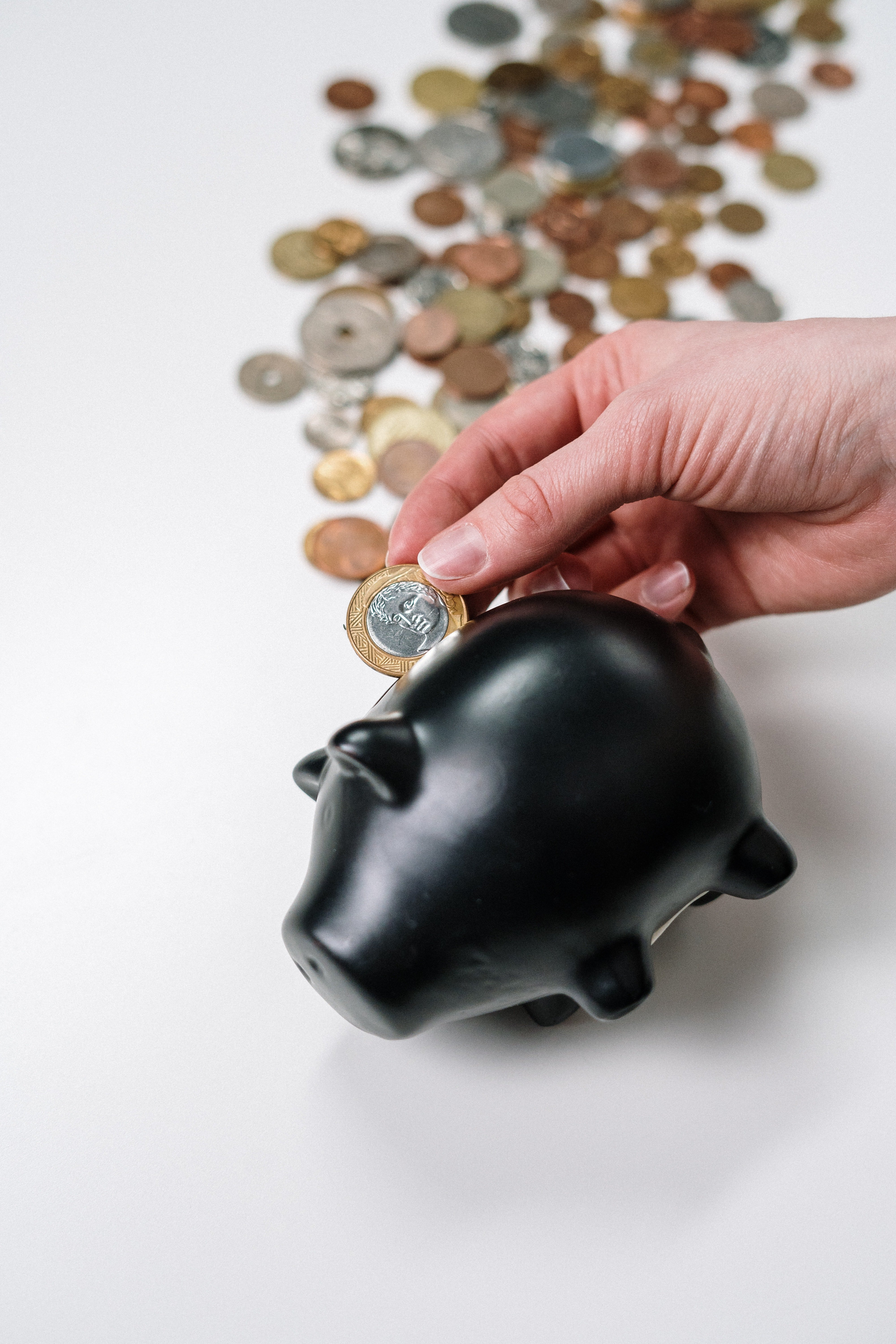 Person takes coins from a piggy bank |  Photo: Pexels