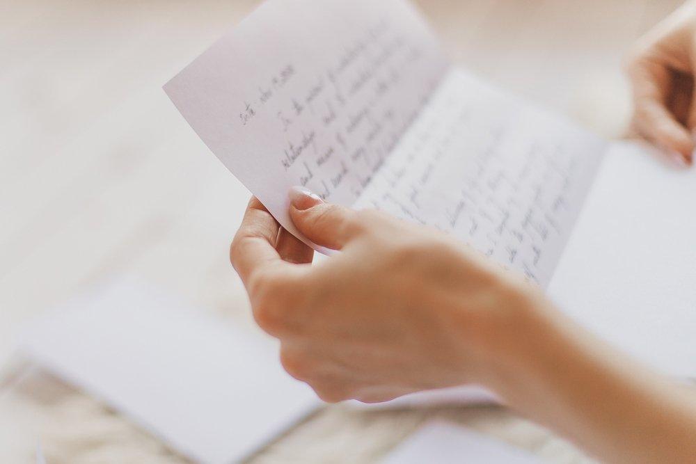 Les mains d'une jeune femme tenant une lettre manuscrite. | Shutterstock