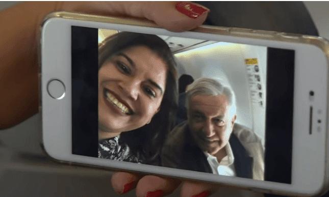 AMLO reflejado en la pantalla del celular de una viajera. | Imagen: YouTube / AFPES