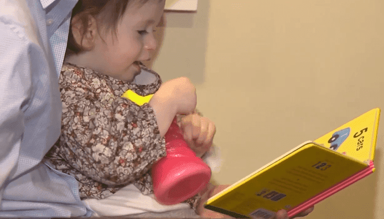 Samantha on her father's lap enjoying a children's book | Photo: ABC 7