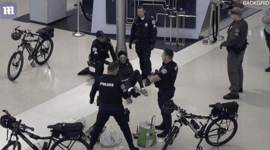 Officers surrounded the woman while one of them checked her belongings.   Photo: Daily Mail/Backgrid
