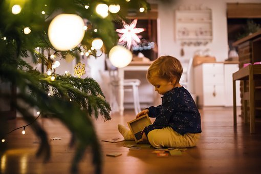 A cute toddler child sitting by Christmas tree at home | Photo: Getty Images