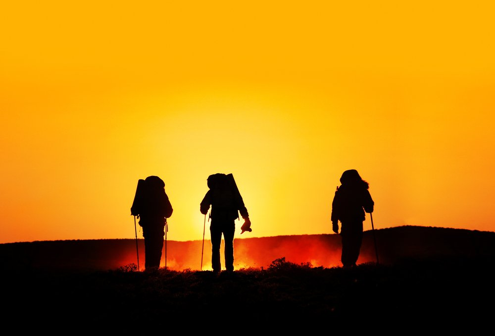 A photo of three people in a desert | Photo: Shutterstock