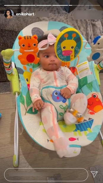 Kevin Hart's daughter, Kaori Mai, dressed in a colorful onesie and a pink bow while seated on a chair | Photo: Instagram/ enikohart