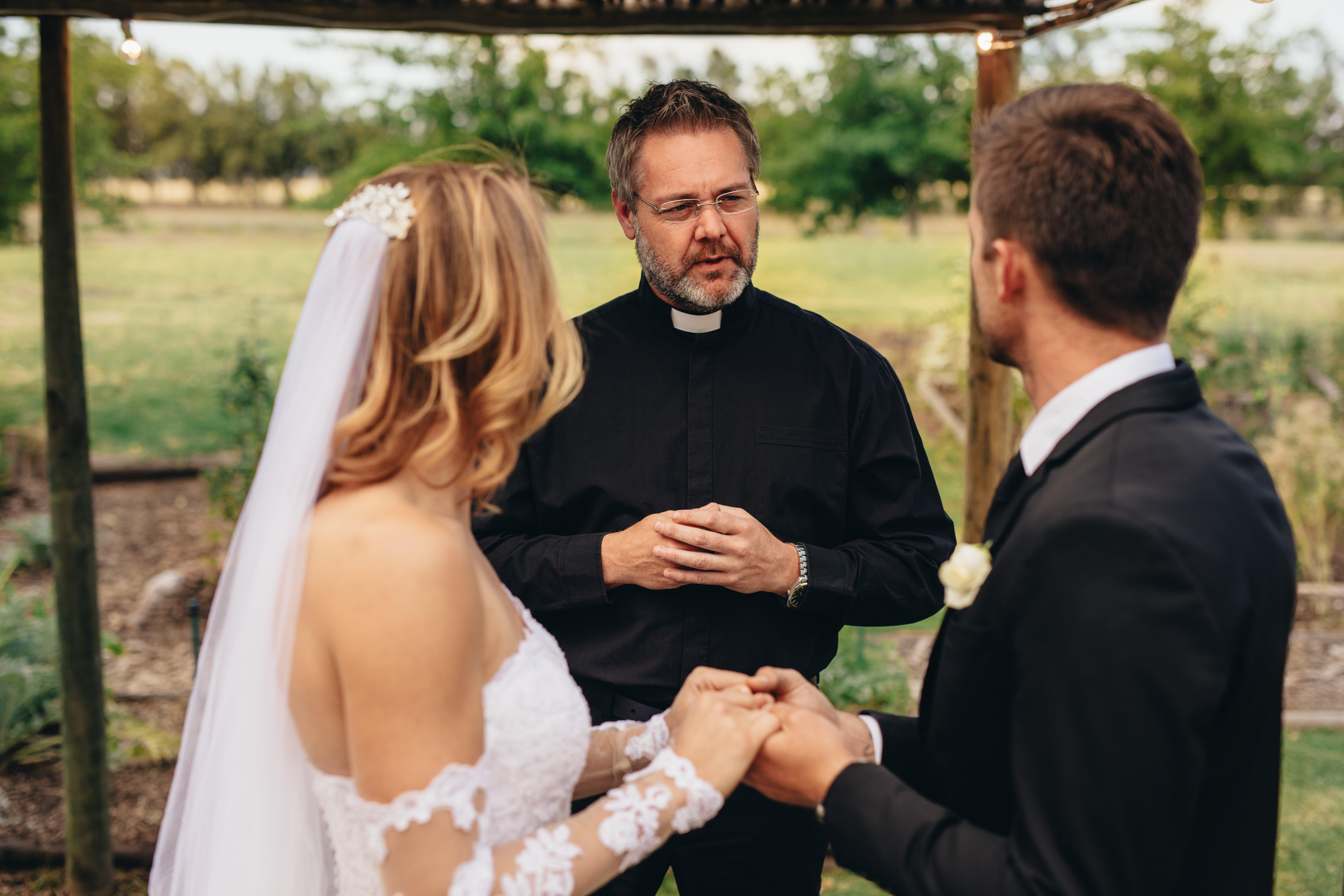 Un prêtre marie un couple lors d'une belle cérémonie de mariage en plein air. | Photo : Shutterstock