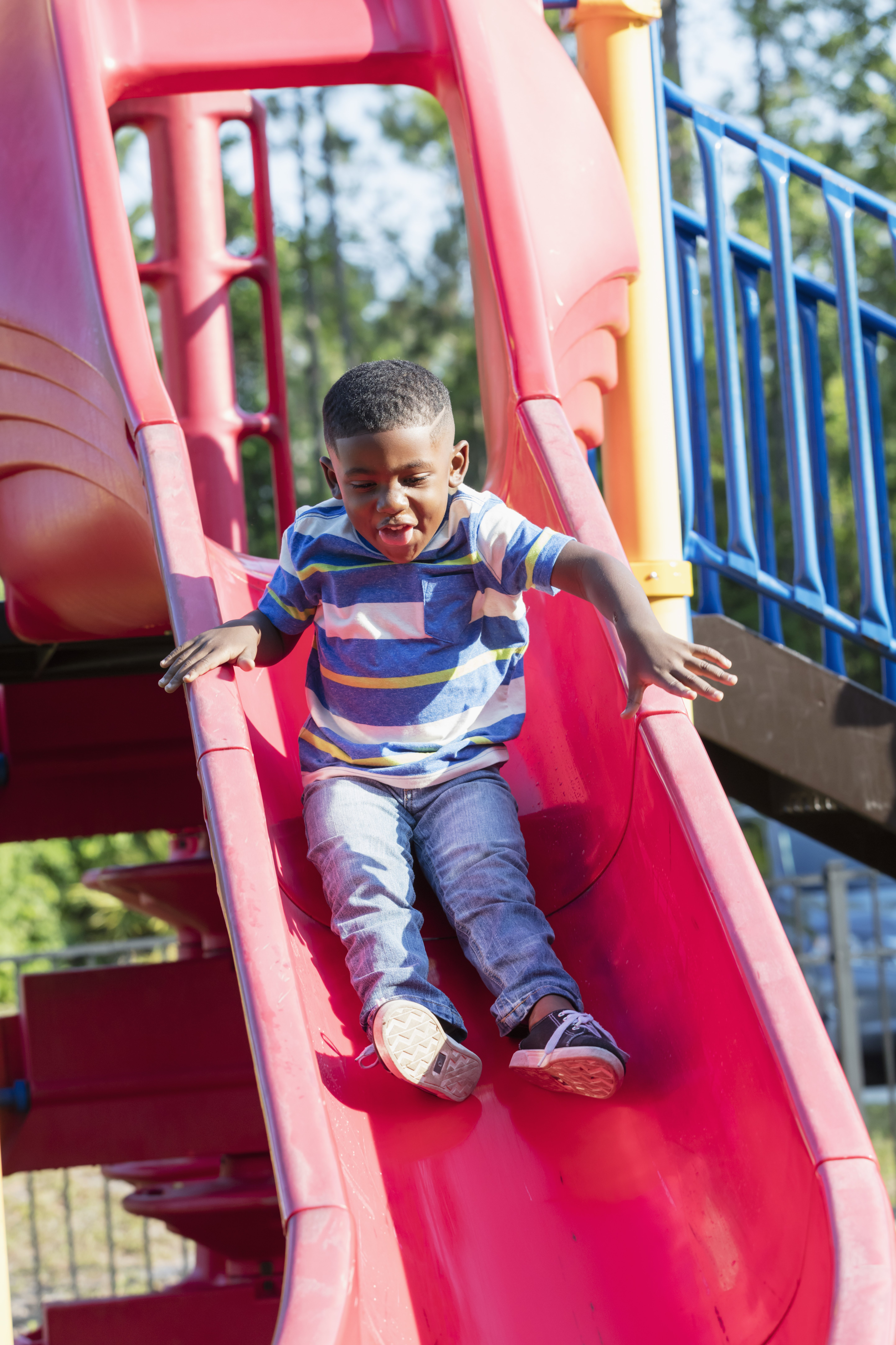 A 4 year old American boy having fun sliding down a slide on a playground at the park or schoolyard. | Photo: Getty Images