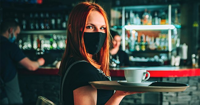 A young woman waitressing while wearing a mask. │Source: Shutterstock