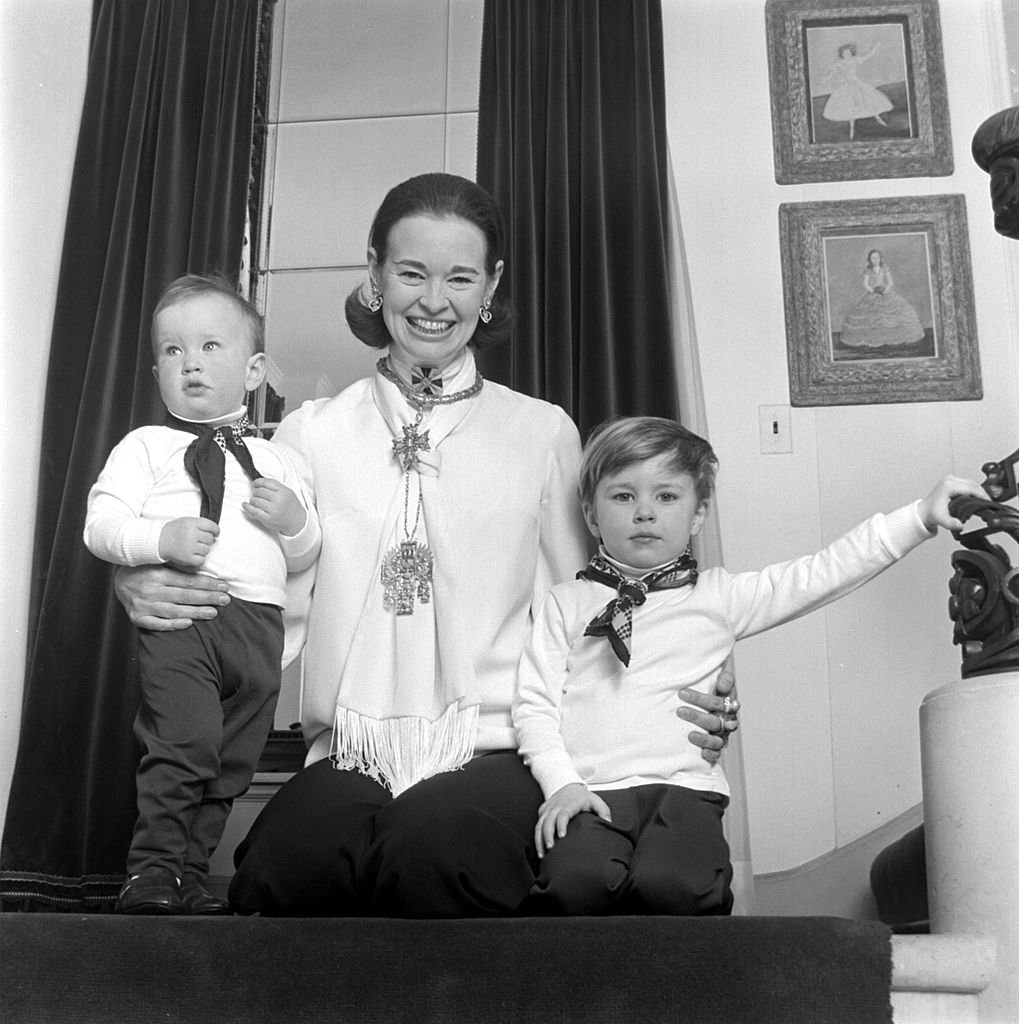 Gloria Vanderbilt poses for a portrait session with her sons Anderson Cooper (L) and Carter Vanderbilt Cooper (R) in their home in circa 1969 in Southampton, Long Island, New York | Photo: Jack Robinson/Hulton Archive/Getty Images