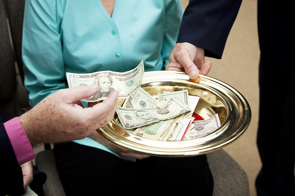 Church members putting money in the collection plate | Photo: Shutterstock