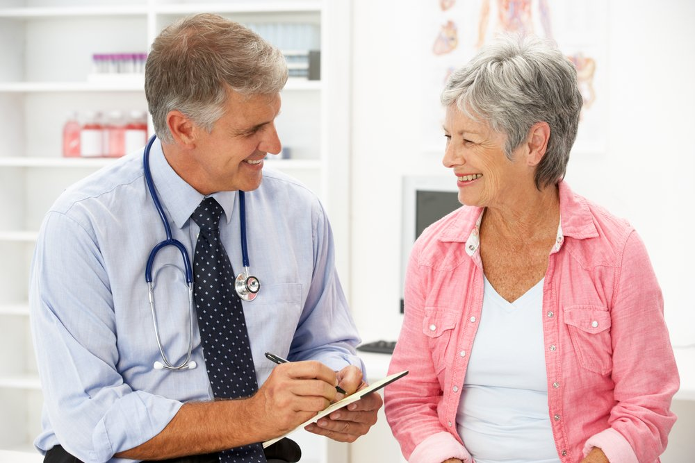 An elderly woman is sitting and discussing with her pharmacist.  |  Source: Shutterstock