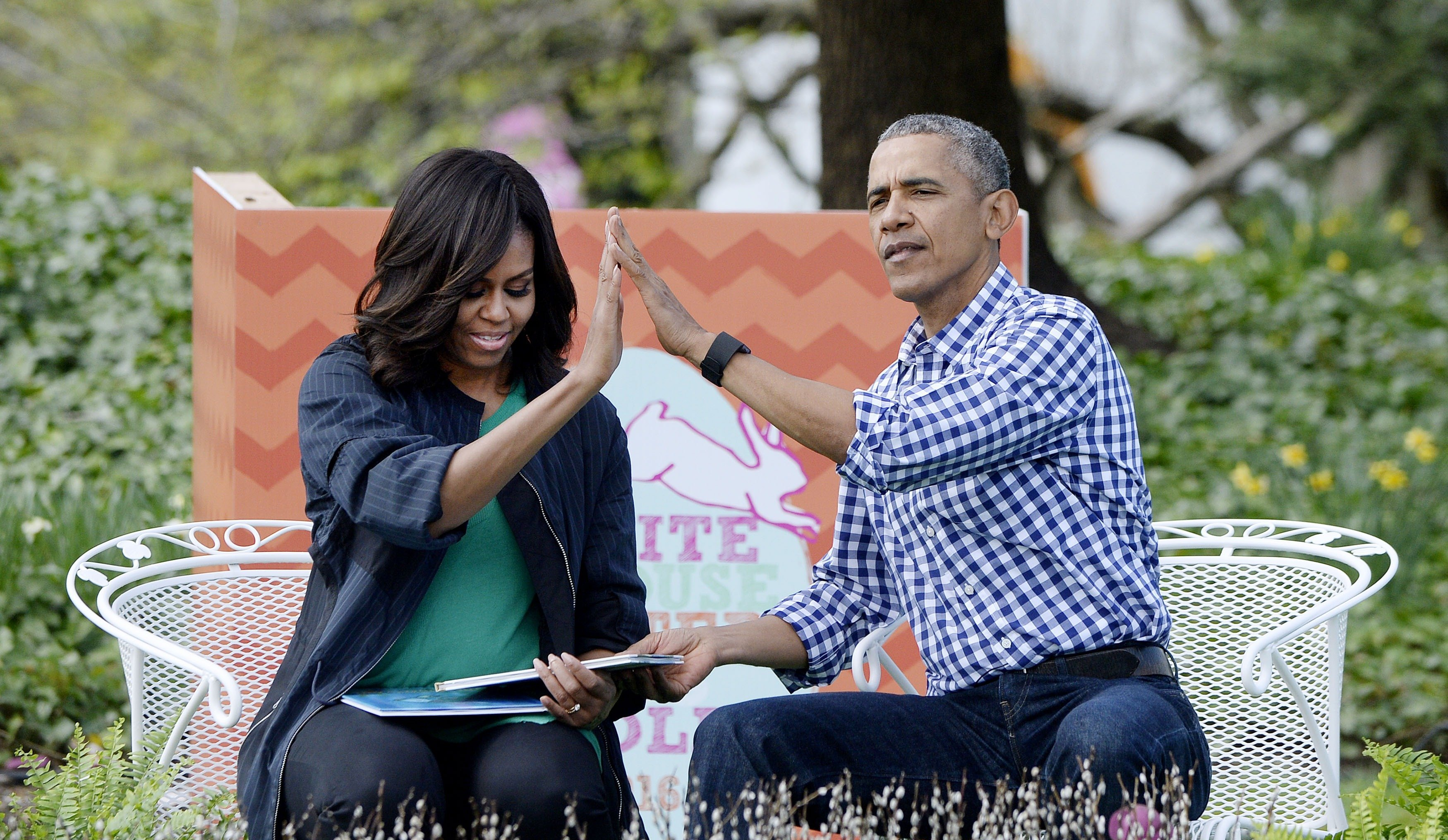 """President Barack Obama (R) and first lady Michelle Obama (L) read """"Where the wild things are""""during the White House Easter Egg Roll on the South Lawn of the White House March 28, 2016, in Washington, DC. 