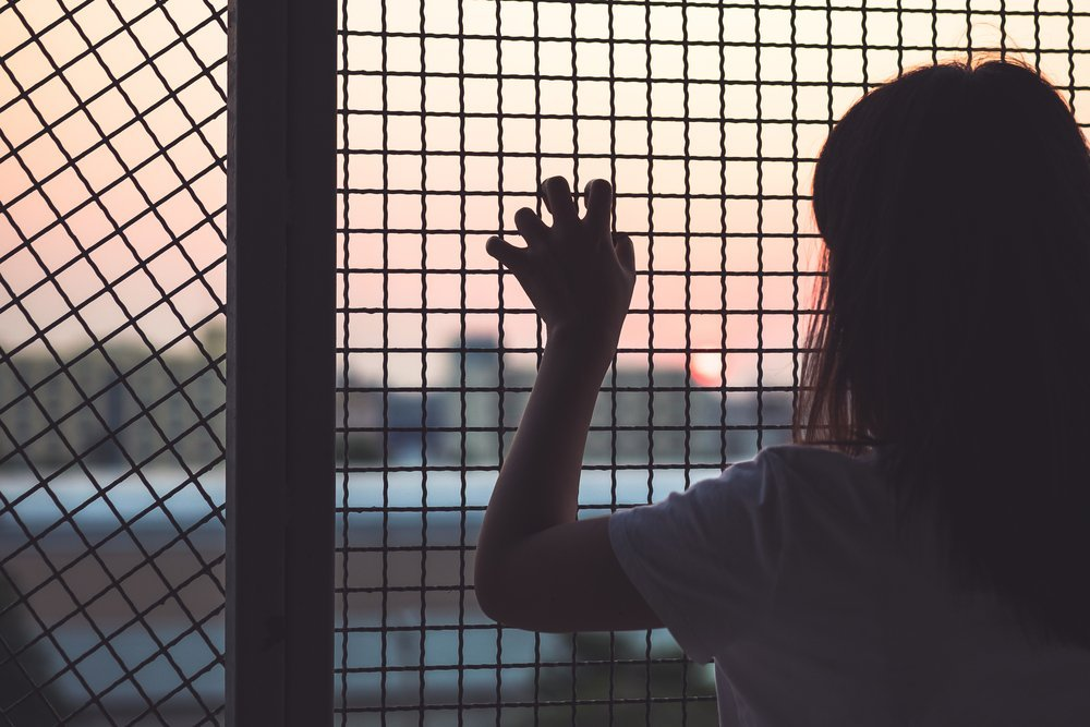 Woman's hand grabs the fence, concept of imprisonment. | Photo: Shutterstock