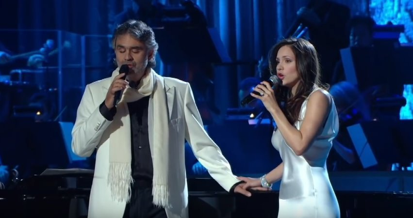 "Music artists Andrea Bocelli and Katharine McPhee hold hands as they sing ""The Prayer"" in front of a live audience back in 2008. 