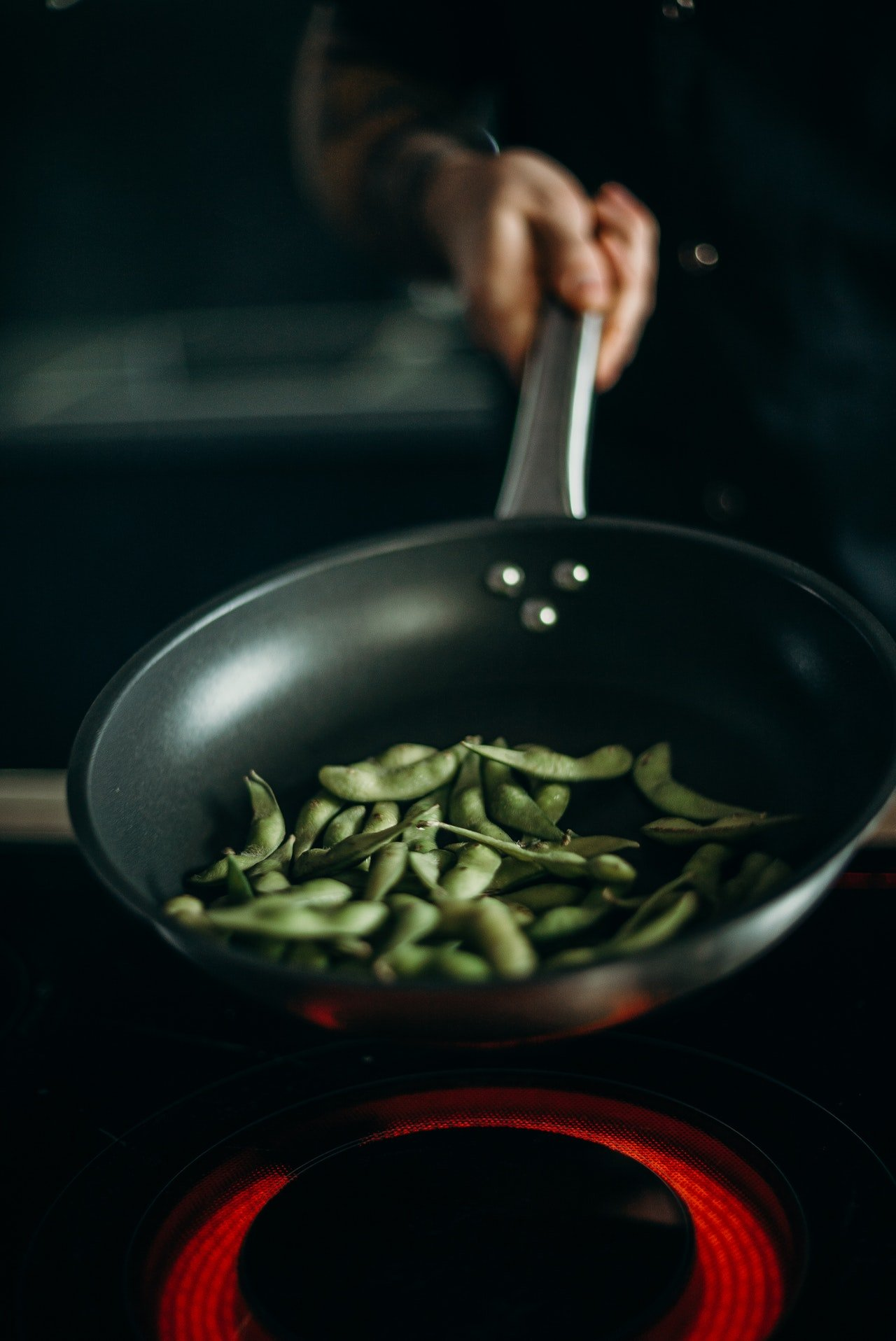 Person holding skillet with green beans | Source: Pexels