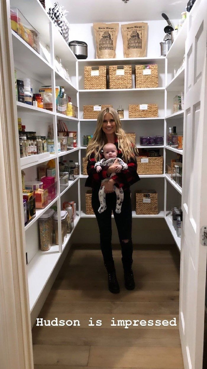 Christina Anstead poses in her professionally organize pantry with her son, Hudson London Anstead | Source: Instagram.com/christinaanstead