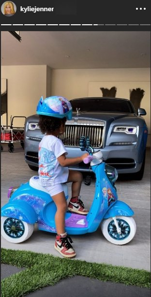 Stormi Webster wearing an helmet on a blue bike | Photo: Instagram/kyliejenner